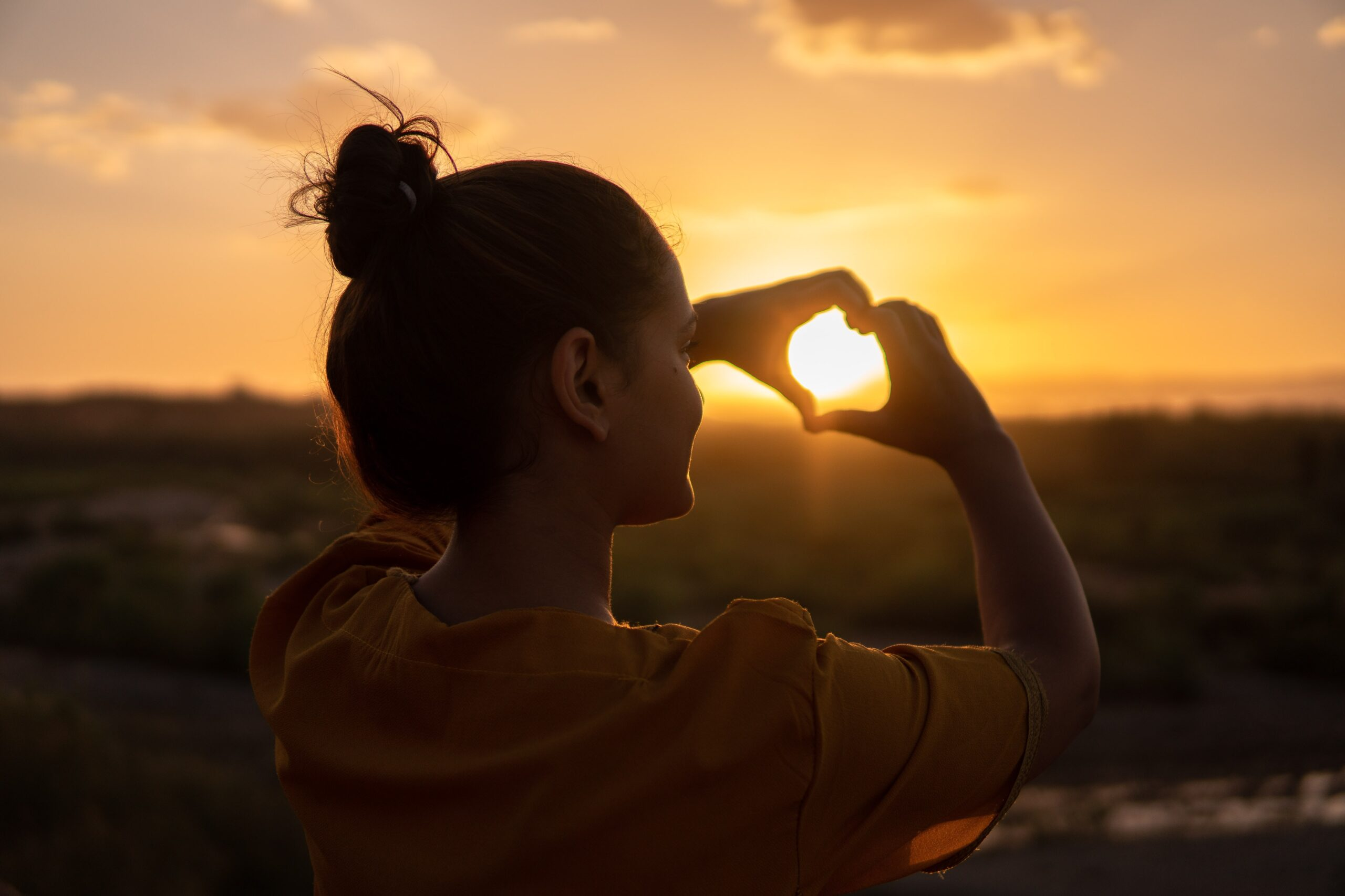 Woman-staring-at-the-sunset-making-a-heart-figure-with-her-hands